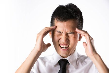 tired worker: Asian business man holding his head. Conceptual image. Stock Photo