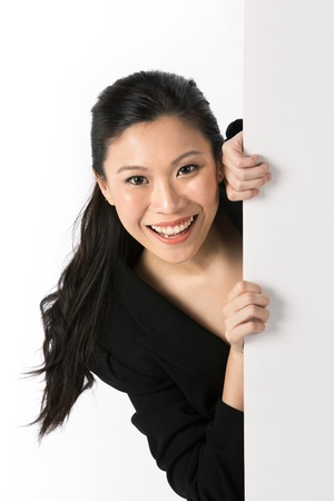 Asian woman peering around from behind a white wall.  photo