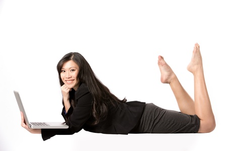 Happy Asian Woman lying down using a laptop. photo