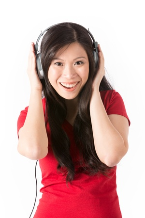 Beautiful Asian woman wearing headphones & listening to the music. photo