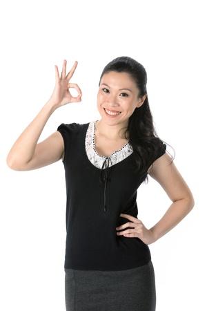 ok symbol: Felice donna asiatica facendo simbolo OK con la mano. Isolato su sfondo bianco.