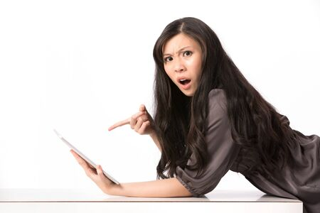 startled: Portrait of a surprised Asian woman pointing at her touch screen tablet.
