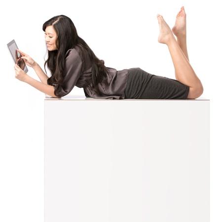 Mujer asiática que miente encima de un blanco cartelera. Aislado sobre fondo blanco.