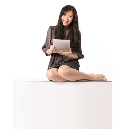 bisiness: Asian Woman sitting on top of a blank billboard sign. Isolated on white background. Stock Photo