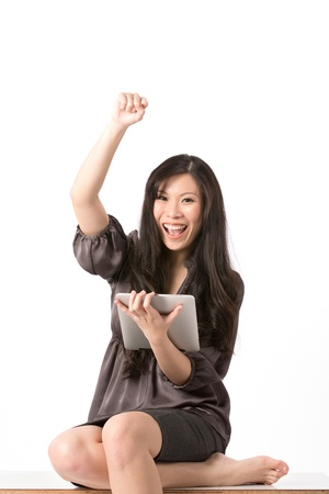 Excited Asian woman using touchpad pc and cheering. photo