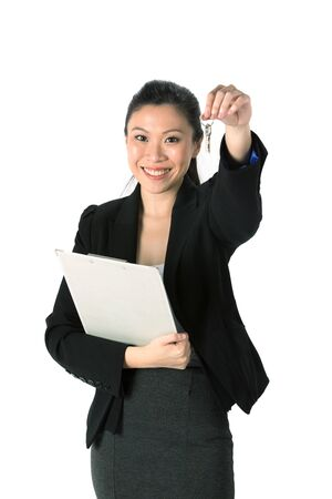 Happy Chinese business woman or realtor showing keys. Isolated over white background.