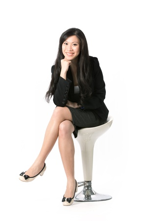 Full length portrait of an Asian Business woman sitting on a chair. Isolated on white background. Stock Photo