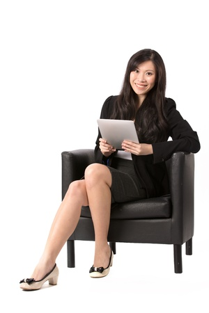 executive chair: Full length portrait of an Asian Business woman sitting on a chair using Digital Tablet. Isolated on white background. Stock Photo