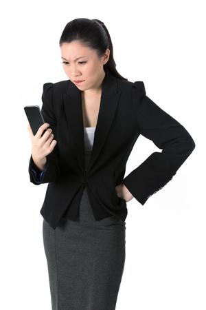 celulas humanas: Enojado joven empresaria de leer las malas noticias en su tel�fono celular. Aislado sobre fondo blanco. Foto de archivo