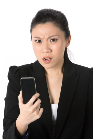 Angry young businesswoman reading bad news on her cell phone. Isolated on white background. photo