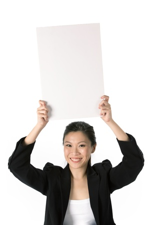 above head: Asian Business woman holding an empty white sign above her head  Stock Photo