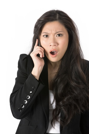 Angry Asian business woman talking on cell phone  Isolated on white  photo