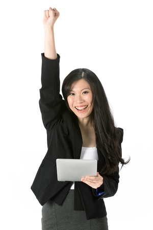 Excited Asian business woman using touchpad pc and cheering  photo