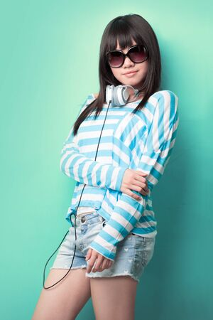 Happy Chinese woman with headphones and sunglasses leaning against a green wall. photo
