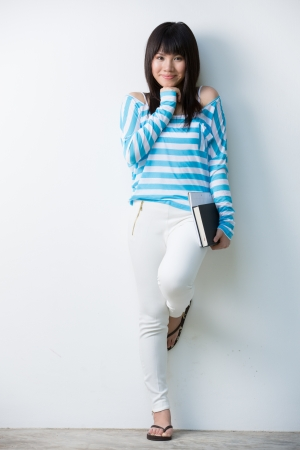 Happy Chinese female student leaning against a wall with a books photo