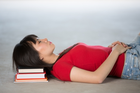 Female College Student Sleeping on pile of books photo