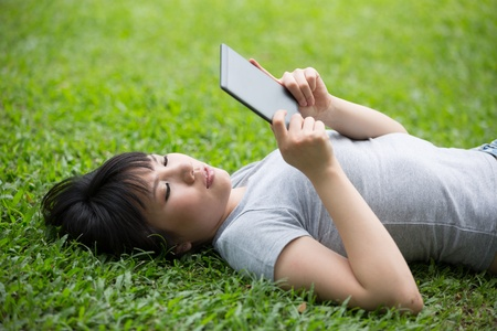 Asian woman is reading her e-book lying on the grass Stock Photo - 14604188