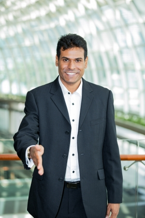Happy Indian business man with his hand out ready to welcome you. photo