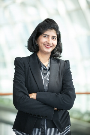 Portrait of a happy Indian business woman standing with folded arms. photo