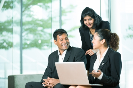 laptop stand: Happy Indian Business team working together around a laptop Stock Photo