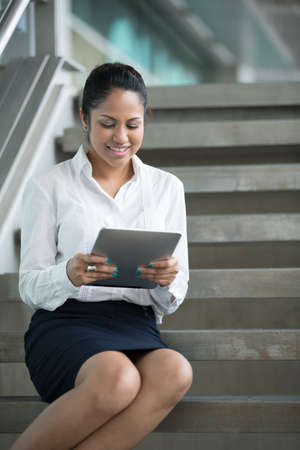 Portrait of a happy Asian business woman using a tablet PC. Stock Photo - 14604181