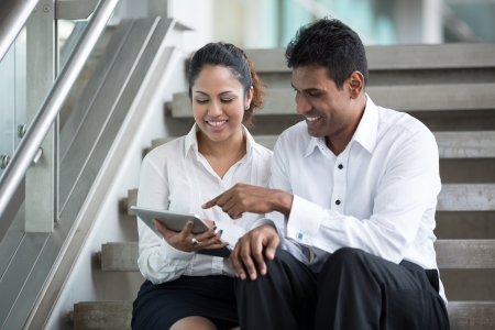 Happy Indian Business man and woman looking at a digital\ tablet.