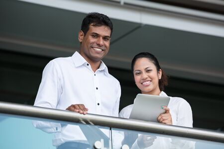 Happy Indian Business man and woman looking at a digital tablet. photo
