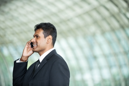 Portrait of handsome Indian business man using cell phone. photo