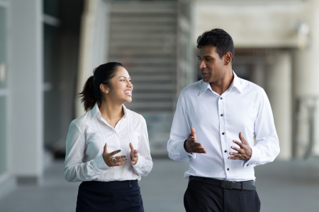 conversation: Happy Indian Business colleagues walking outside office & talking to each other.