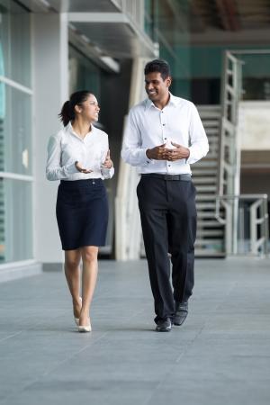 personas caminando: Feliz colegas de negocios indio camina fuera de la oficina, hablando el uno al otro. Foto de archivo