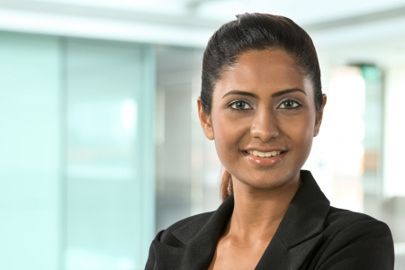 business woman standing: Portrait of a happy Indian business woman. Stock Photo