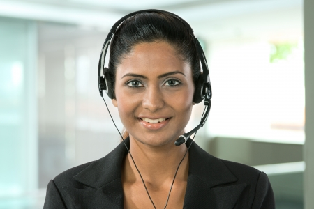 telephonist: Portrait of a happy young Indian female call centre employee with a headset. Stock Photo