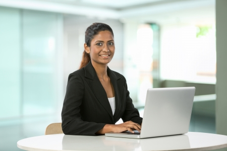 copyspace corporate: Portrait of a happy Indian business woman using on laptop.