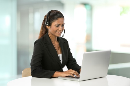 call center office: Portrait of a happy young Indian female call centre employee with a headset. Stock Photo