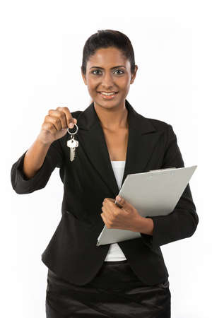 Happy Indian business woman or realtor showing keys. Isolated over white background. photo