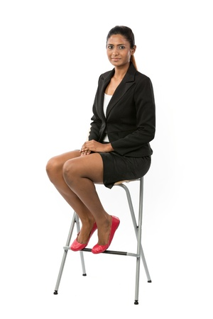 the stool: Full length portrait of an Asian Business woman sitting on a chair. Isolated on white background. Stock Photo