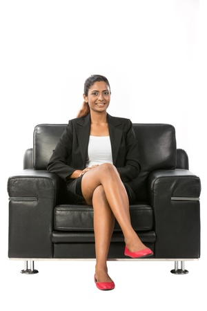 Happy young Indian Businesswoman sitting on a chair. Isolated on white background. photo