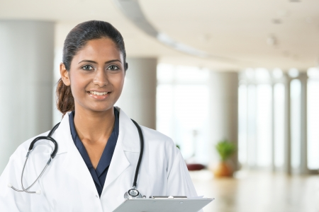 Indian doctor wearing a white coat with stethoscope. The photo has been composed so there is plenty of space for text on the right. photo