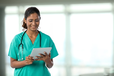 personal medico: M�dico indio Mujer mirando una tableta digital y lleva un estetoscopio matorrales verdes m�s.
