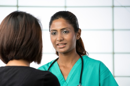 Indian doctor talking with female patient in doctors office. Stock Photo - 14840662