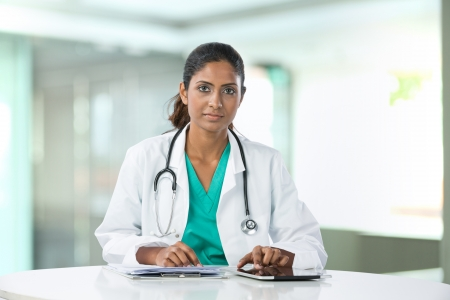 asian doctor: Female Asian doctor sitting at a table using a digital tablet.