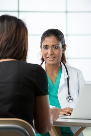 nurse and patient: Indian doctor talking with female patient in doctors office.