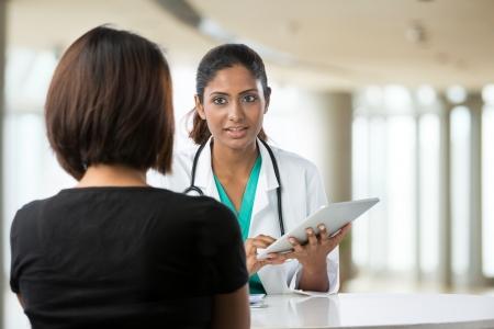 consulta médica: Médico indio que habla con el paciente femenino en la oficina de los médicos.
