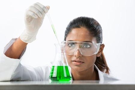 asian woman face: An Indian scientific researcher looking at a liquid solution. The background has been Isolated.