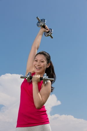 energetic people: Asian woman exercising with dumb bell weights outside. Stock Photo