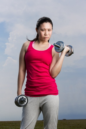 dumb: Asian woman exercising with dumb bell weights outside. Stock Photo