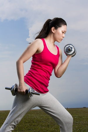 Asian woman exercising with dumb bell weights outside. photo