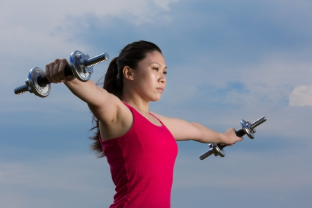 weightlifting equipment: Asian woman exercising with dumb bell weight outside during the summer. Stock Photo
