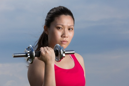 Asian woman exercising with dumb bell weight outside during the summer. photo