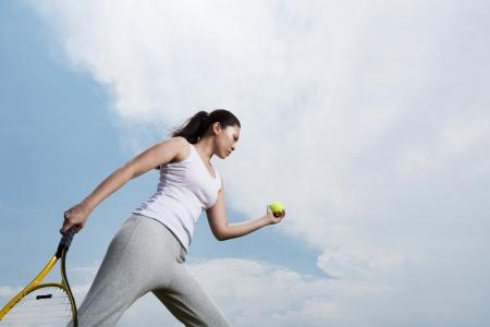 jugando tenis: Mujer asi�tica jugando tenis a punto de servir la pelota.